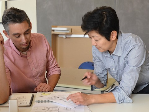 Product designers Cutter Hutton and Ayako Takase review a design drawing.