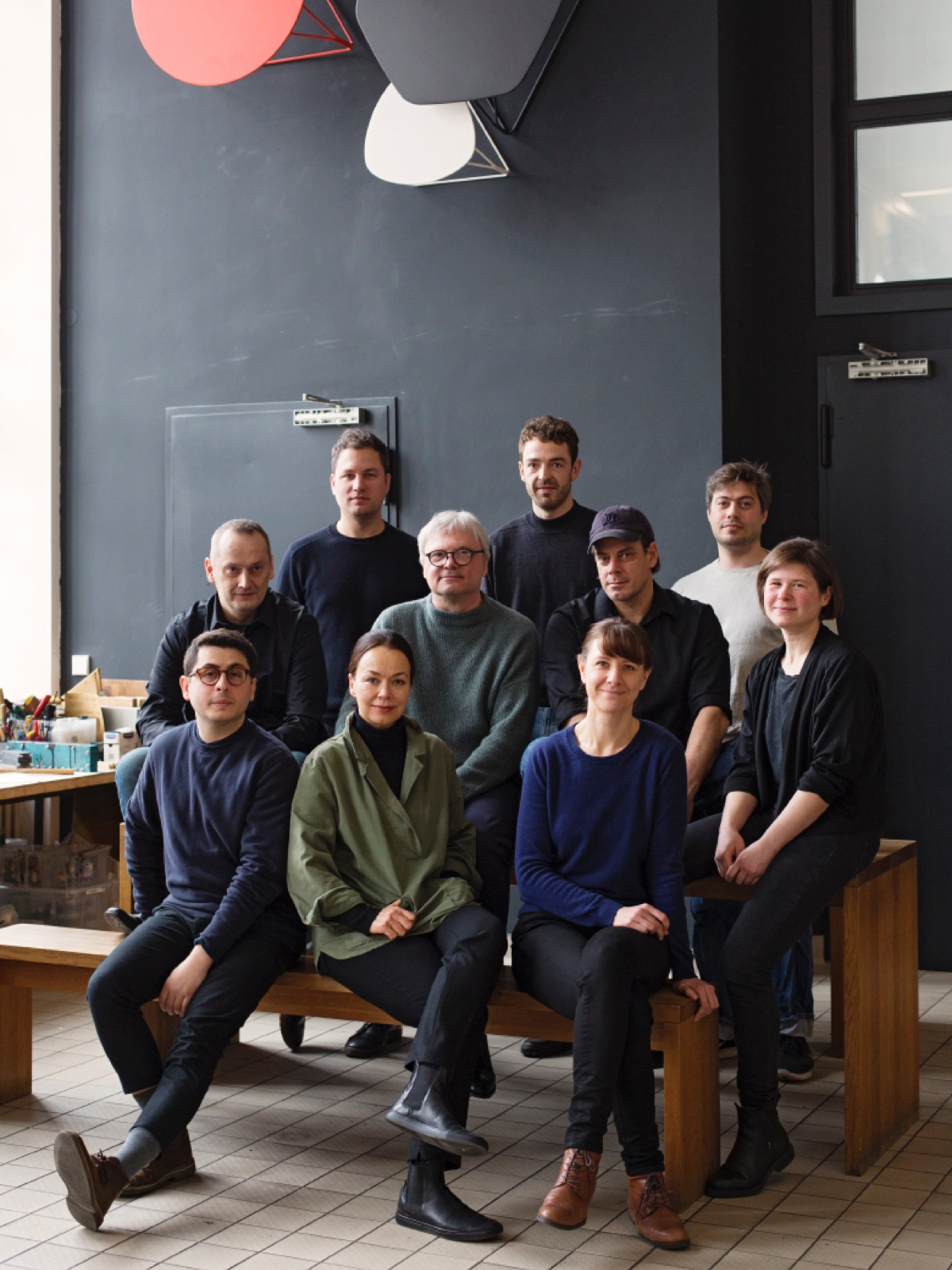 The men and women of Studio 7.5 sit grouped together on wooden benches in their workspace.