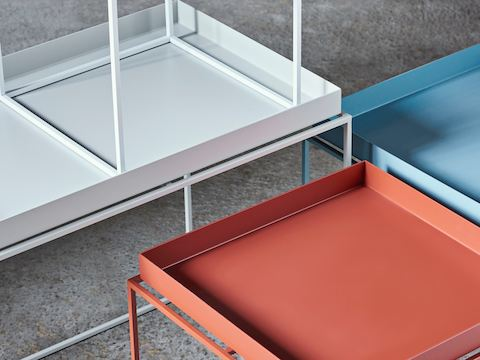 A close-up image of white, orange, and light blue tray tables.