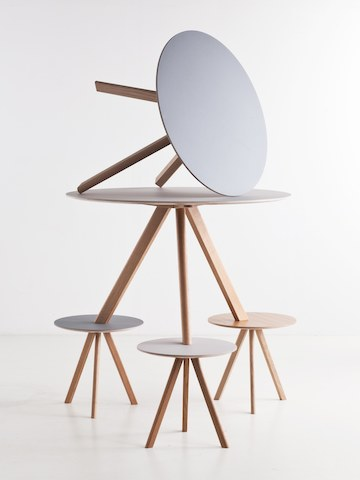A round coffee table with white top and wooden legs on its side sits at the top of a pyramid of matching tables.