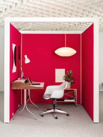 A three-walled enclosure within a larger white office space features bright red walls, white trim, and an open ceiling with a hanging white Nelson Bubble Lamp. Inside are a wooden secretary Nelson Swag Leg Desk, a white Eames Task Chair, and small console with plant. Select to learn more about Overlay.