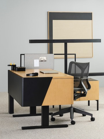 A wood desk with geometric black accents connected to a low wood storage unit and black metal T-bar light with a dark gray Cosm chair and laptop computer with desk accessories.