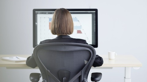 A woman with her back to the camera sits in a dark gray Aeron work chair at a wooden sit-to-stand desk with large computer monitor, notebook, and white coffee cup. Select to learn more about Live OS.