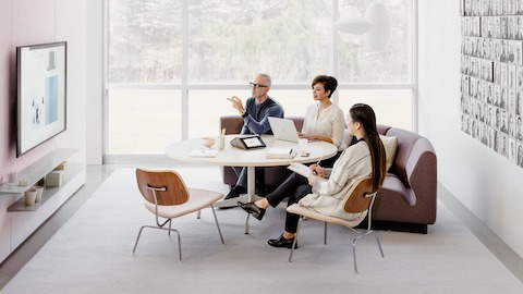 A bright office space with a maroon Chadwick Modular Seating sofa surrounding a round wooden Eames Table and upholstered light pink Eames Plywood Dining Chairs with metal bases. Three coworkers look on to a TV mounted on the wall. Select to go to Living Office Settings.