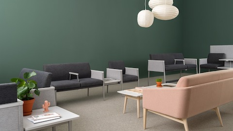 A row of two-toned gray guest chairs with attached tables sit on a sage green wall while a blush pink sofa and white coffee table with matching pale wood legs face the row. Select to go to Nemschoff's Palisade Collection.