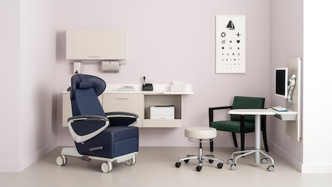A dark blue patient reclining chair sits in front of a light wooden wall-mounted sink and cabinet system. Next to it is a tan upholstered stool, dark green and black guest chair, and white side table on wheels. Select to go to Mora System.