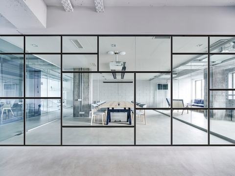 A large glass and black metal wall with a modern geometric pattern separates two open white spaces with a large wooden conference table and upholstered gray chairs. Select to learn more about Maars.