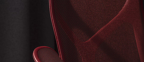 Close-up of a dark red Cosm chair featuring the back and armrest on a black background.