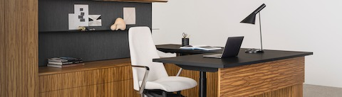 A veneered wood desk and cabinet is topped with matte black counters and backed with a dark gray wall and shelf. A white executive chair pulls up to the desk, which features a laptop, black task lamp, and open book.