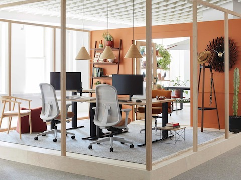 An indoor/outdoor office space with sit-to-stand desks, and Lino office chairs, hanging Hay pendant lamps, and potted cacti.