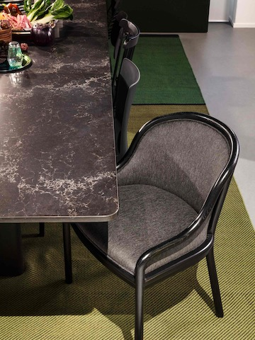 A close-up image of a black Landmark Chair next to a Geiger Axon black marble-top table.