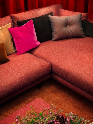A close-up image of a red Lecco Open Sectional with pillows in pink, grey, and gold.