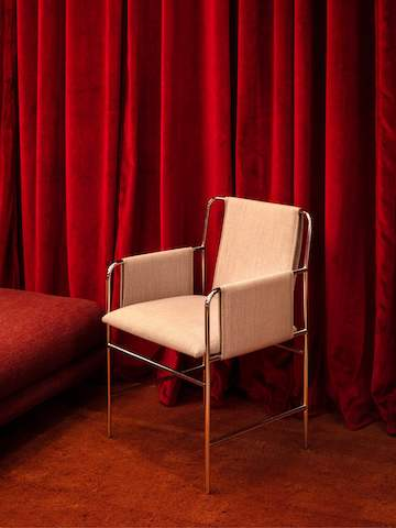 A close-up image of an Envelope Chair in tan upholstery against red curtains.