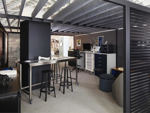 A maker studio created with Overlay with dark gray walls, a stainless steel Quovis Standing-Height Table, black Revolver Stools, a Procedure Cart with Meridian Storage, and a Hay About a Chair in the corner.