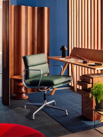 An Eames Soft Pad Management Chair in a wooden, private office setting with an Eames Walnut Stool in the back.