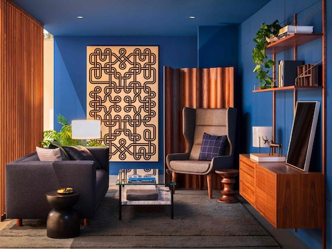 A private space containing a Hush Chair in a corner face a glass Layer table and a sofa, a Knot Girard Environmental Enrichment Panel hanging on a blue wall, and an Eames Molded Plywood Screen on the side.