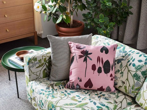 A close-up image of a Lispenard Sofa in botanical print with pillows next to a green Tulou Coffee Table.