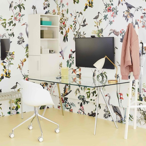 A close-up image of a clinician's office with floral wallpaper, a glass-topped Magis Baguette Table, a white Taper Chair, a white Magis Steelwood Coat Stand, and a gray Palissade bench.