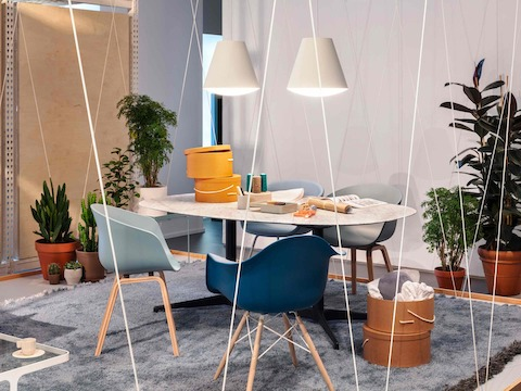 An office space with About A Chairs and Eames Molded Plastic Chairs in shades of blue pulled up to a white oval Nelson Pedestal Table with a white marble top. Two white Sinker Pendants hang above the table.