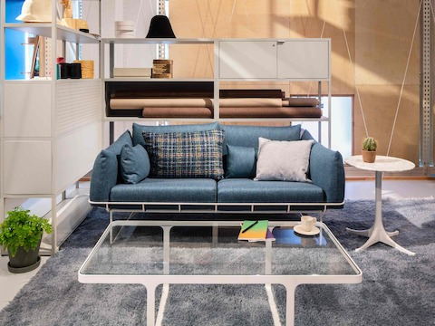 A casual lounge space showing a blue Wireframe Sofa with several pillows facing a rectangular Trace Coffee Table and a Magis Steelwood Shelving Unit behind it.