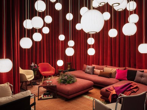 A lounge space containing a large, red Lecco Open Sectional with an ottoman; a multitude of Nelson Bubble Lamps hanging from the ceiling; a mix of red, pink, and brown textured pillows; Eames Walnut Tables with flowers; and two Hay About A Lounge Chairs in orange and cream.