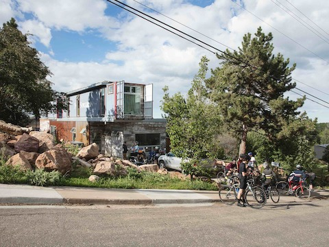 Bicyclists gather outside a modern house in Boulder, Colorado.