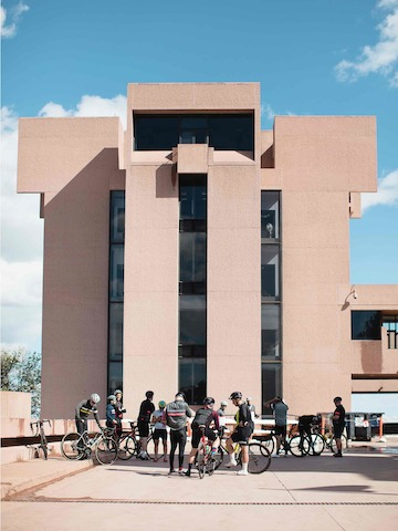 Dismounted bicyclists interact outside Boulder's Mesa Laboratory, designed by modernist architect I.M. Pei.