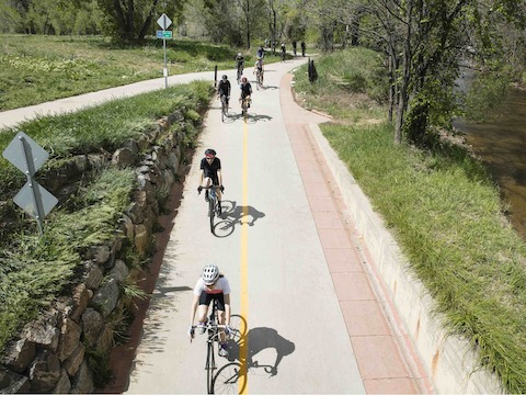 Bicyclists take a fork in the road next to a stone wall.