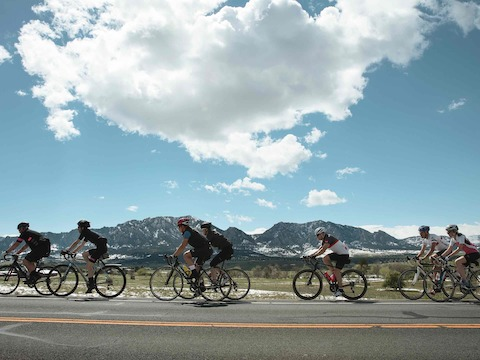 Several bicyclists pedal alongside a highway with the foothills of the Rocky Mountains in the distance.