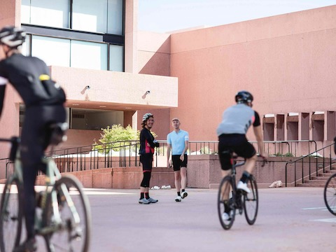 Four bicyclists—two standing and two riding—outside a modern building.
