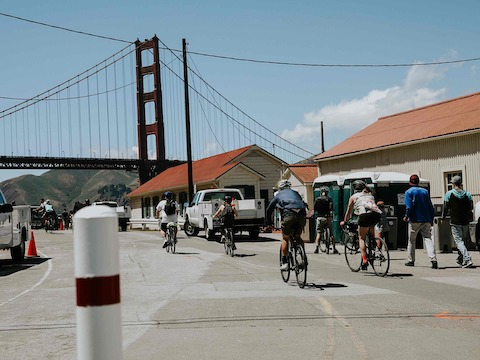Bicyclists pedal toward the Golden Gate Bridge.