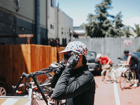 A dismounted bicyclist adjusts a riding cap.