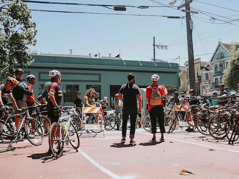 Dismounted bicyclists on an architecture tour listen to their guide in a San Francisco neighborhood.