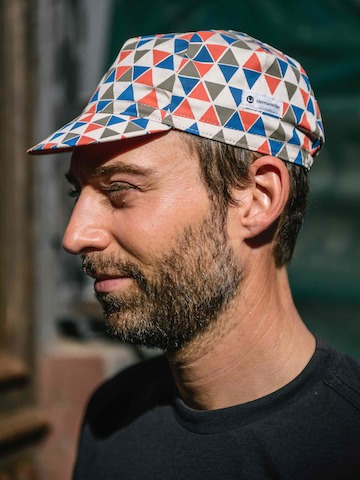 Profile of a man wearing a colorful cycling cap inspired by midcentury designer Alexander Girard.