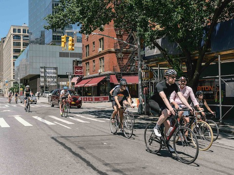 Bicyclists pedal past a Manhattan intersection.