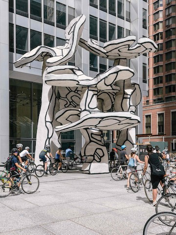 Bicyclists gather at the base of Jean Dubuffet's Group of Four Trees sculpture in New York.