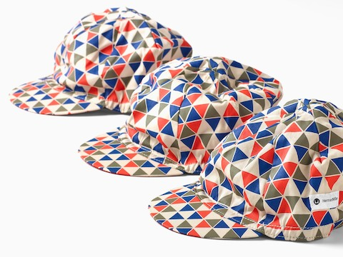Three cycling caps featuring colorful triangles inspired by a print from midcentury designer Alexander Girard.