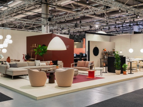 A view of Herman Miller's booth in the Stockholm Furniture Fair with various settings featuring two Lína Swivel Chairs, a Nelson pendant lamp, a Crosshatch Settee, and an orange Geiger I Beam Side Table.