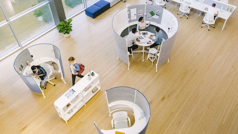 An overhead view of an open office with people working in two Prospect Solo Spaces and a Prospect Collaborative Space. Select to go to the Prospect product page.