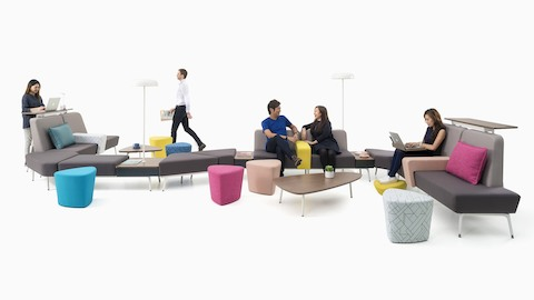 Employees work and interact on a curved configuration of Sabha Collaborative Seating. Select to go to the Sabha product page.
