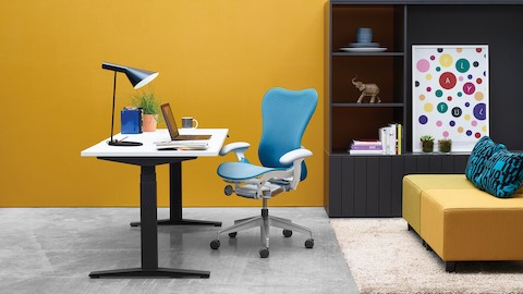 An Augment Ratio sit-to-stand desk with a blue Mirra 2 office chair. Select to go to the Augment Ratio product page.