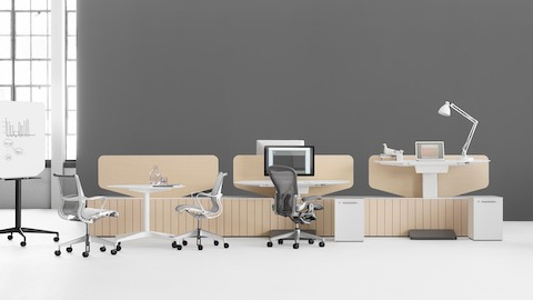A collaborative workplace featuring a Locale workbase and sit-to-stand tables. Select to learn about Sit-Stand surfaces.