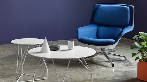 A blue Striad Lounge Chair with two occasional tables. Select to learn about the Herman Miller Collection.