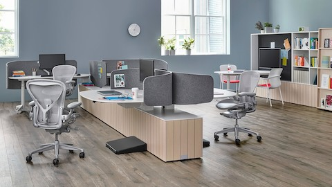 Light grey Aeron office chairs in a collaboration area featuring Locale workstations. Select to go to the Aeron product page.