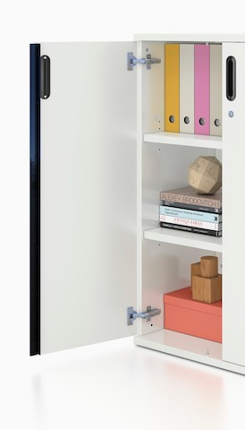 Partial view of an open hinged-door Paragraph Storage unit, showing books and binders inside. Select to go to the Storage product page.