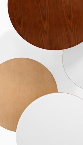 Overhead view of four overlapping round tabletops in various finishes. Select to go to the Tables product page.