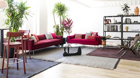 A red Bolster sofa and settee anchor a residential setting that includes stools, plants, and bookshelves.