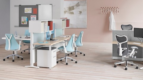 An open healthcare administrative area featuring light blue Sayl Chairs and gray Mirra 2 Chairs. Select to go to the Clinical products page.