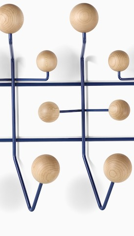 Close-up of an Eames Hang-It-All with wood knobs for hanging storage. Select to go to the Accessories product page.