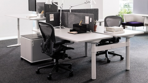 An open office with Atlas Office Landscape workstations and black Aeron Chairs.